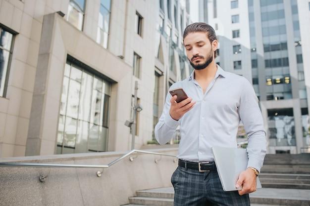 Ruhiger und konzentrierter junger geschäftsmann steht auf stufen und schaut auf das telefon. er hält den laptop in der linken hand. guy ist von gebäuden umgeben.