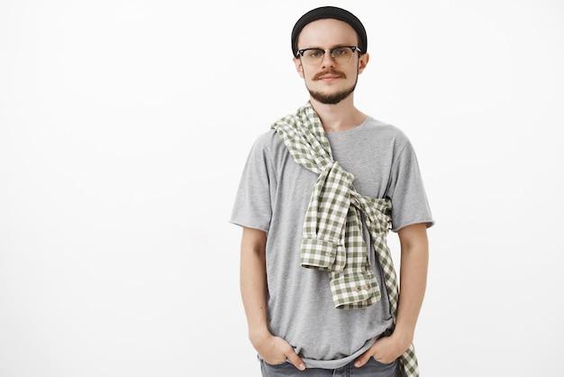 Ruhiger und kühler kreativer europäischer mann mit bart in gläsern und schwarzer mütze, die hände in den taschen hält, die vor gleichgültigkeit grinsen und vor gleichgültigkeit herumblicken