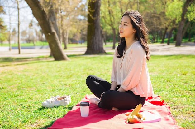Ruhiges asiatisches mädchen, das im park sich entspannt