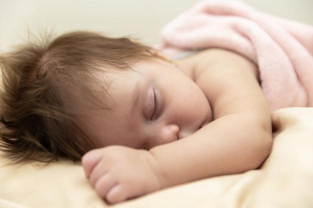 Ruhiges baby, das auf einem bett beim schlafen liegt