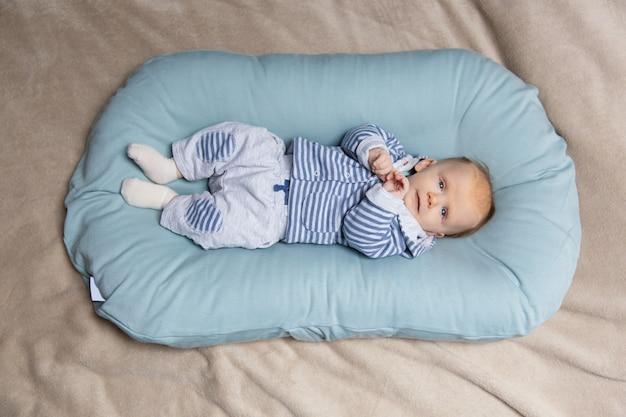 Ruhiges entzückendes baby, das auf matratze liegt
