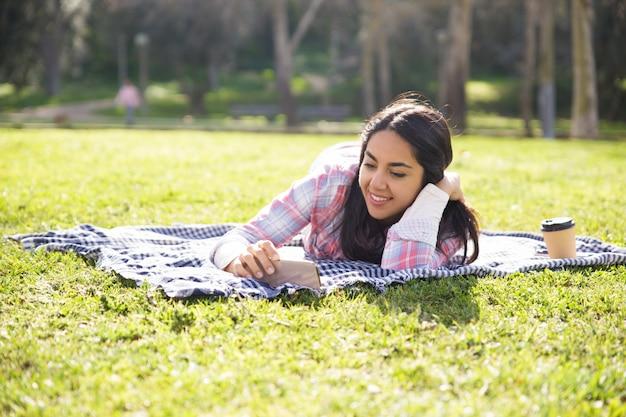 Ruhiges erfreutes mädchen, das im park sich entspannt