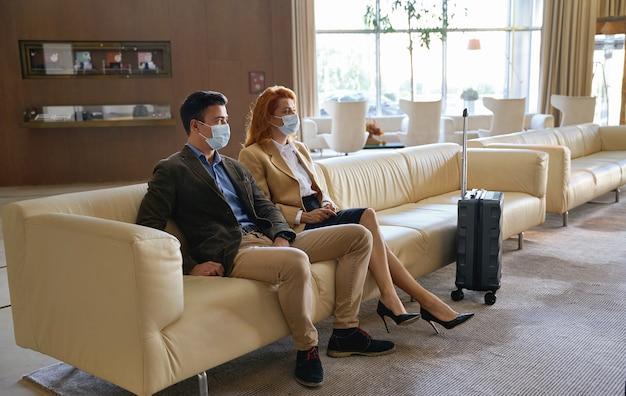 Ruhiges erwachsenes paar, das medizinische masken trägt, während es auf einem sofa in einer hotelhalle mit einem kinderwagenkoffer sitzt