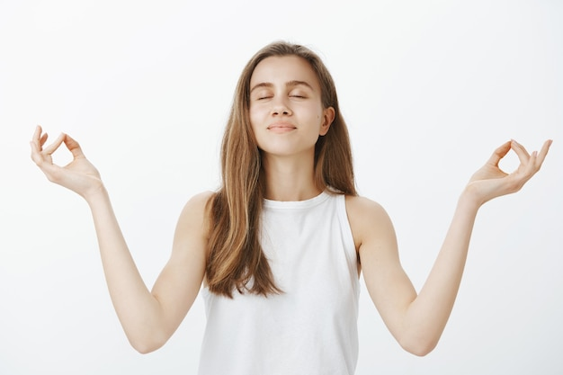 Ruhiges hübsches mädchen, das meditiert und sich während des yoga entspannt