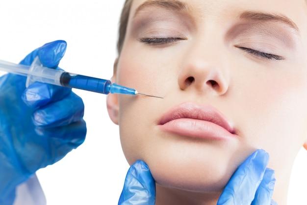 Ruhiges hübsches modell, das botox einspritzung über den lippen hat