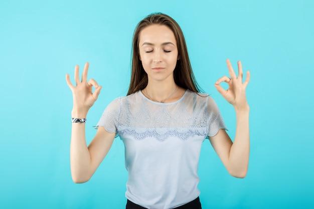 Ruhiges junges schönes mädchen übt atmungsyogaübungen, meditiert innen, schließt augen
