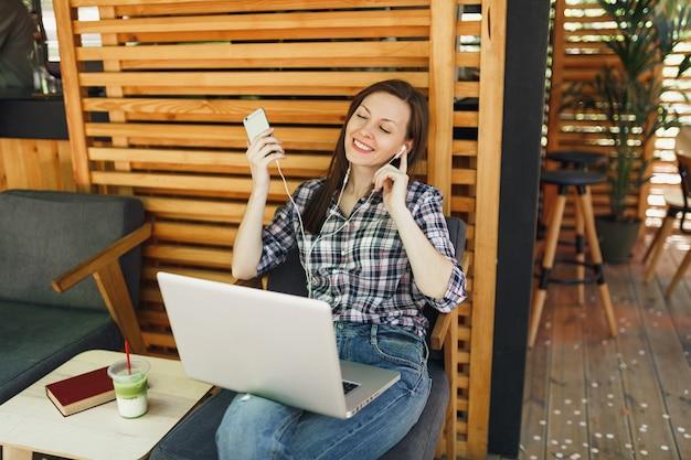 Ruhiges mädchen im sommercafé im freien aus holz, das mit einem modernen laptop-pc-computer, handy sitzt