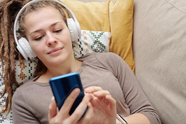 Ruhiges mädchen mit dreadlocks, die musik in kopfhörern hören und im smartphone scrollen, während sie sich auf der couch entspannen