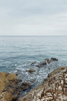 Ruhiges meer, das sanft auf die felsen schlägt