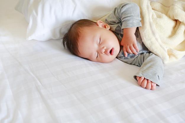 Ruhiges neugeborenes asiatisches baby, das auf bett mit der decke schläft.