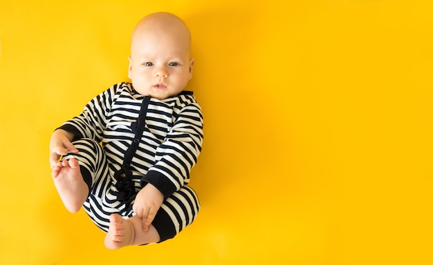 Ruhiges neugieriges baby, das auf gelbem hintergrund liegt, draufsicht, kopienraum