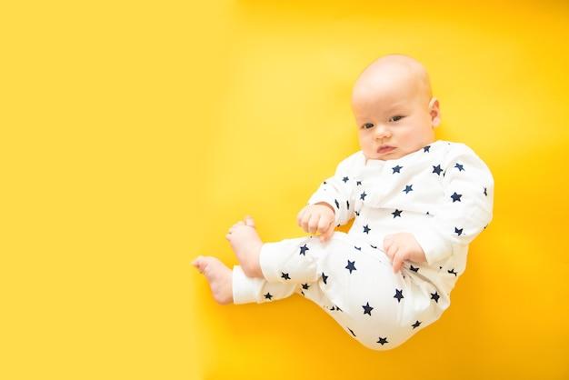 Ruhiges neugieriges baby, das auf gelbem hintergrund liegt und kamera, draufsicht, kopienraum betrachtet
