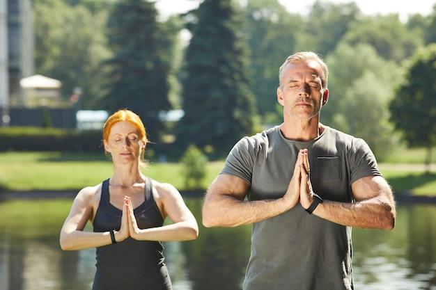 Ruhiges reifes paar mit geschlossenen augen, die hände in namaste halten und zusammen am fluss im stadtpark meditieren