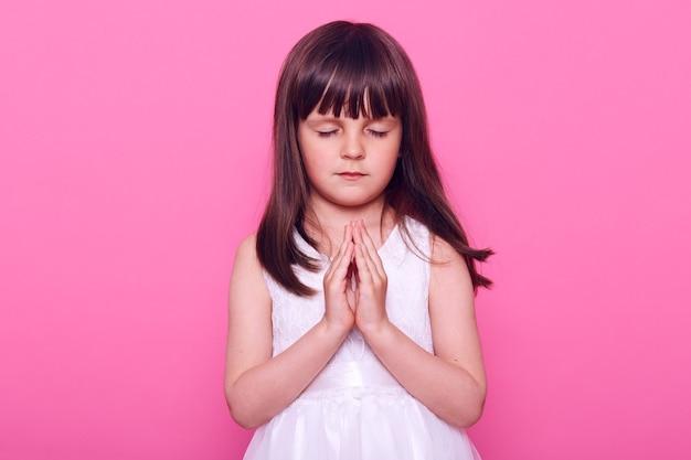 Ruhiges schönes kleines mädchen im weißen kleid, das yoga praktiziert, augen geschlossen hält, handflächen zusammenpresst, dunkelhaariges süßes kind betet, hoffnung ausdrückt, isoliert über rosa wand