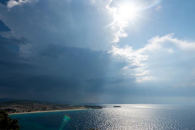 Ruhiges tropisches meer unter sich verdunkelnden gewitterwolken am horizont