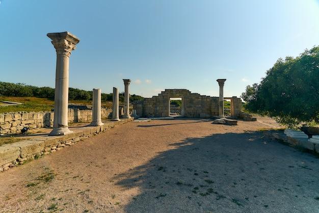 Ruinen eines antiken griechischen tempels in den strahlen der untergehenden sonne