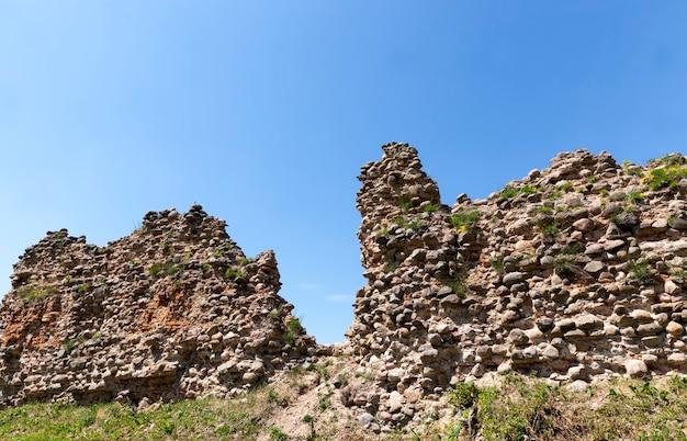 Ruiniert und überwuchert mit grasruinen einer alten festung und steinen und ziegeln, ruinen von verteidigungsstrukturen des mittelalters