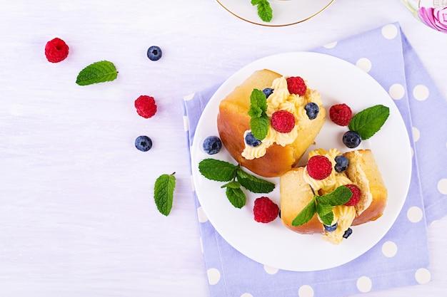 Rum baba dekoriert mit schlagsahne und frischer himbeere, blaubeere. savarin mit rum, sahne und beeren. italienische küche. draufsicht