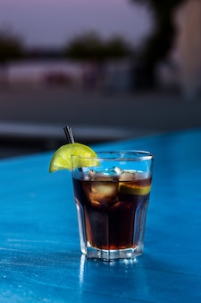Rum-cola-lässiger cocktail mit eiswürfeln und limette am sommerbarstandhintergrund