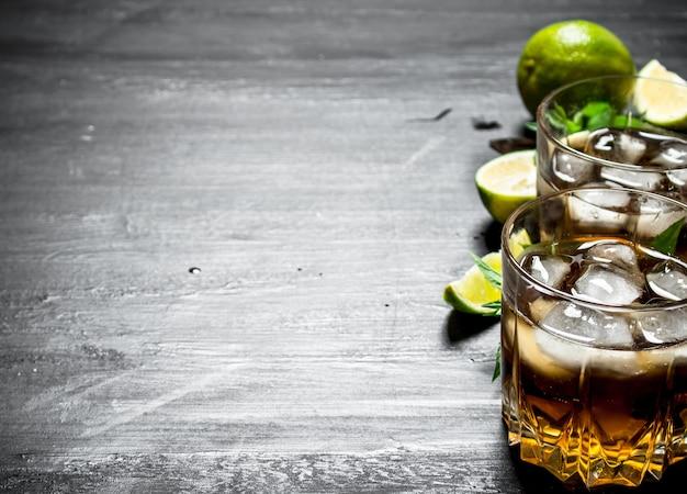 Rum mit eis, minze und frischer limette. auf einem schwarzen hölzernen hintergrund.