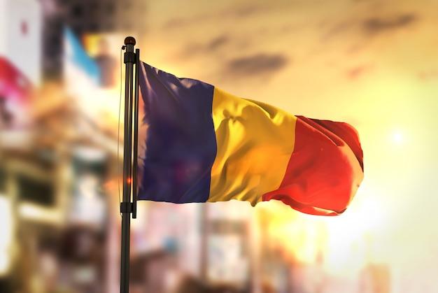 Rumänien flagge gegen stadt verschwommen hintergrund bei sonnenaufgang hintergrundbeleuchtung