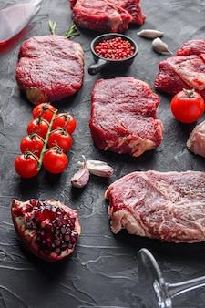 Rump, rindersteak schneidet, vor top blade steak mit kräutern, gewürzen und rotweinglas auf schwarzem tisch, seitenansicht.