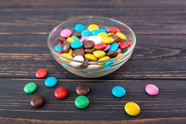 Runde farbige bonbons in einer glasplatte auf einem hölzernen hintergrund.