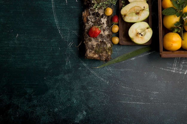 Runde fruchtplatte mit birnen, apfel und beeren auf mattem hintergrund