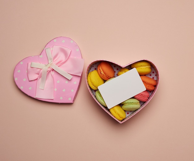 Runde gebackene mehrfarbige macarons liegen in einem rosa karton in form eines herzens