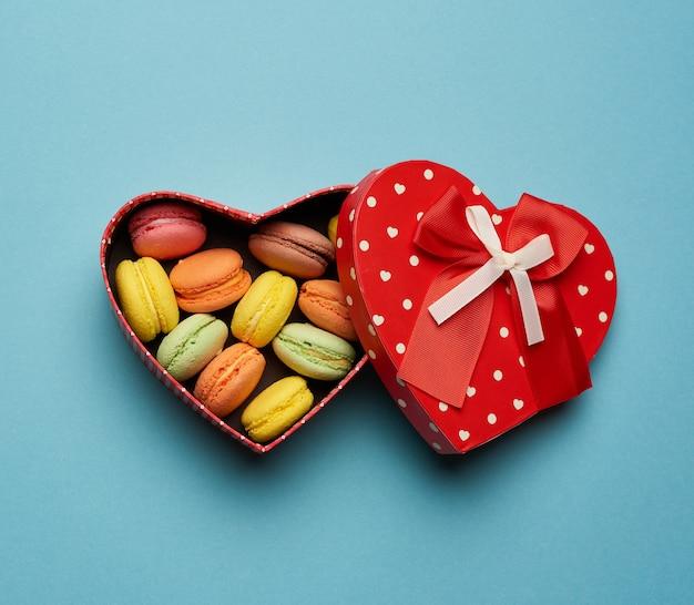Runde gebackene mehrfarbige macarons liegen in einem roten karton