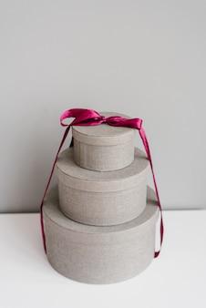 Runde geschenkboxen mit lila satinband auf einem grauen gebunden