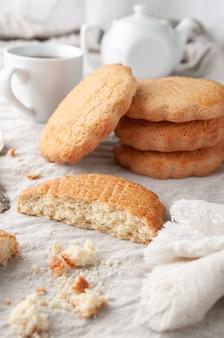 Runde hausgemachte shortbread-kekse. in zwei hälften gebrochen. auf einem leinentischtuch von grauer farbe. im hintergrund ist ein stapel kekse. weiße teekanne und tasse.