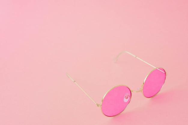 Runde hipster-sonnenbrille mit rosa gläsern und goldenem rahmen. modeaccessoire für frauen