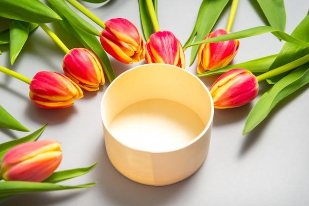 Runde holzkiste und tulpenblumen auf grauem hintergrund