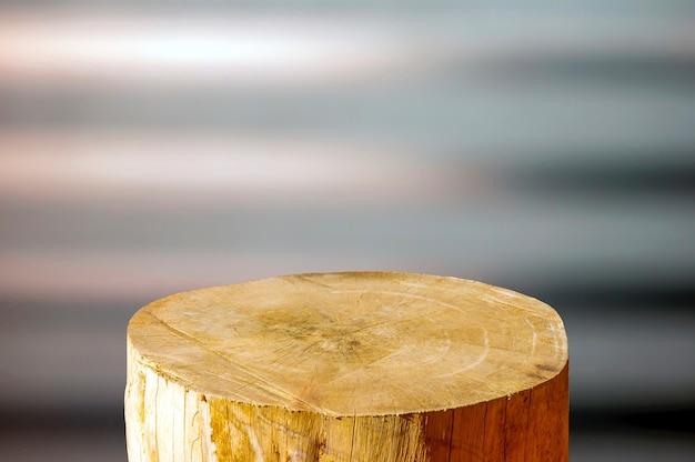 Runde holzsägenschnittzylinderform für produktpräsentation mit weichem braunem und grauem abstraktem hintergrund
