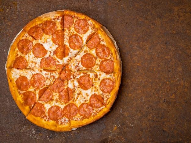 Runde italienische pizza pepperoni auf einer rostigen metalltischplattenansicht, leerer raum für text.