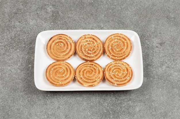 Runde kekse mit sesam auf weißem quadratischem teller