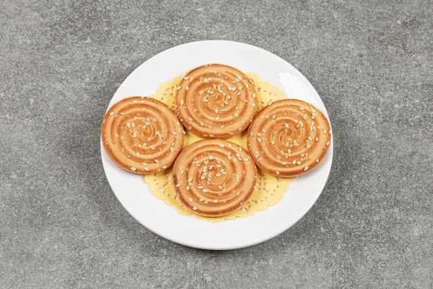 Runde kekse mit sesam auf weißem teller