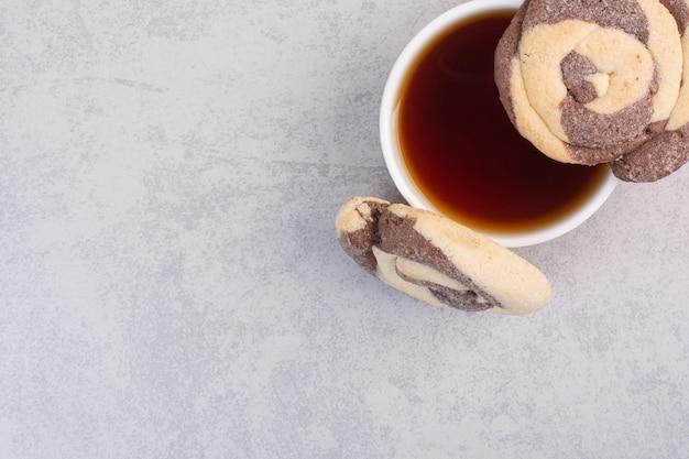 Runde kekse und eine tasse tee auf grauem hintergrund. foto in hoher qualität
