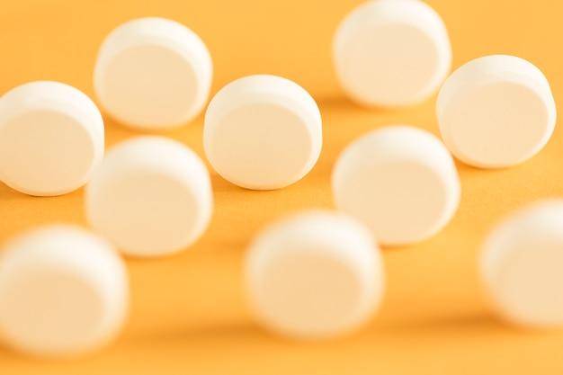 Runde kreisförmige weiße pillen, die auf gelbem hintergrund stehen