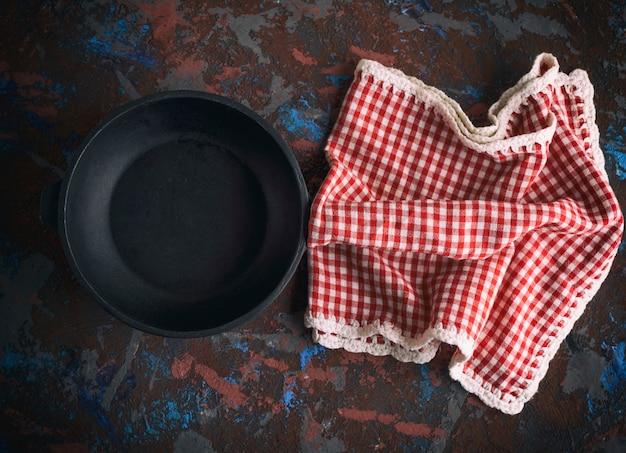 Runde leere schwarze gusseisenbratpfanne mit einer roten serviette in einem roten kasten