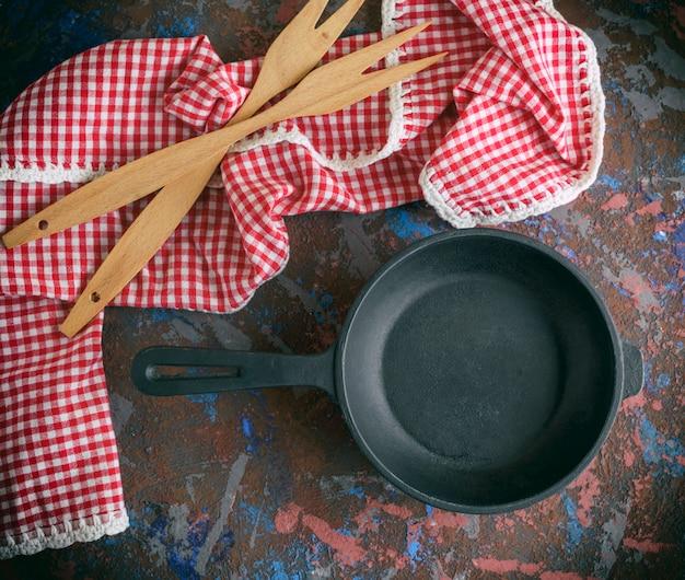 Runde leere schwarze gusseisenbratpfanne mit einer roten serviette