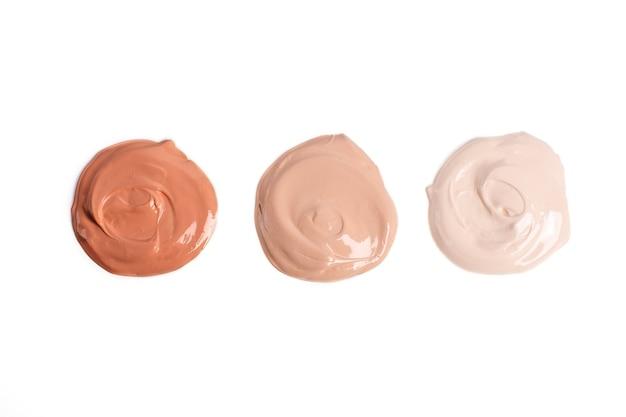 Runde muster flüssiger foundation in verschiedenen farbtönen auf weißem hintergrund