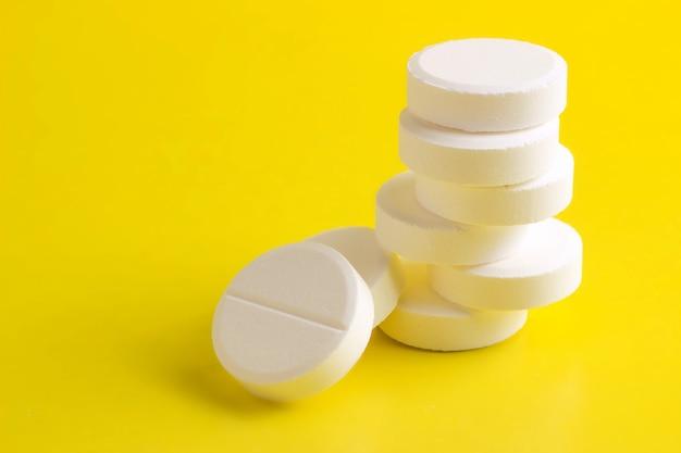 Runde pillen auf gelbem grund gestapelt