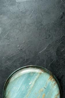 Runde platte mit blick auf die obere hälfte auf schwarzem tisch mit freiem platz