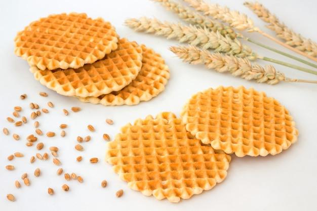 Runde quadratische kekse, weizenspitzen und körner auf weißem tisch