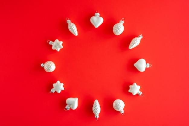 Runde rahmenzusammensetzung mit weißem glas des weihnachtsbaums spielt auf rotem papier. flache lage, draufsicht, kopienraum.