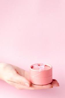 Runde rosa geschenkbox in den händen der frauen auf einem rosa hintergrund. festliches konzept zum valentinstag, muttertag oder geburtstag