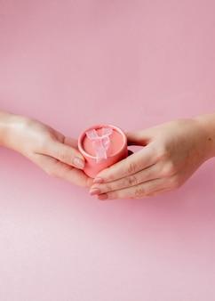 Runde rosa geschenkbox in frauenhänden auf einem rosa hintergrund. festliches konzept für valentinstag, muttertag oder geburtstag.