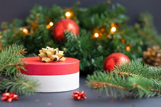 Runde rote geschenkbox mit goldband und kugeln. überraschung, geschenk auf weihnachtsdekoration.